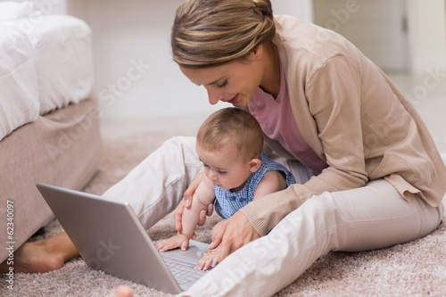 Mother teaching baby to use laptop