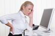 Frau mit Rückenschmerzen im Büro