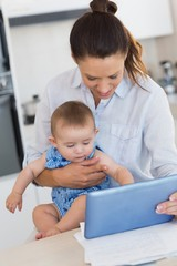 Mother calculating finances while holding baby at counter
