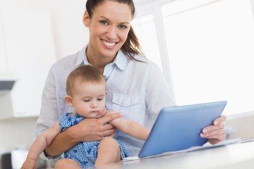 happy mother calculating finances while holding baby