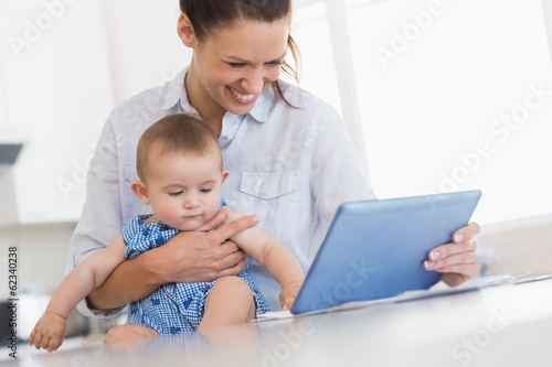 Mother calculating finances while holding baby boy