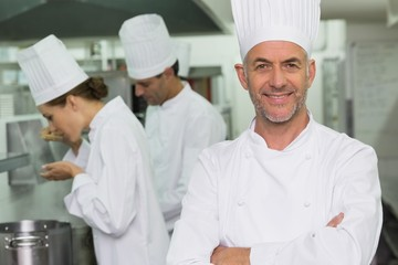 Happy chef looking at camera with team working behind