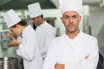 Serious chef looking at camera with team working behind