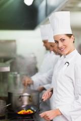 Happy chef smiling at camera while cooking at stove