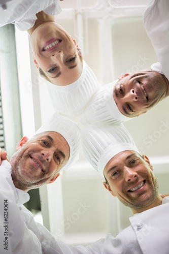 Happy team of chefs standing in a circle