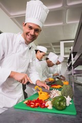 Row of trainee chefs slicing vegetables with one smiling at