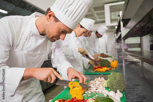 Row of trainee chefs slicing vegetables