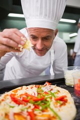 Happy chef sprinkling cheese on a pizza