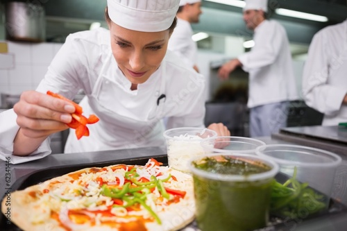 Chef sprinkling pepper on a pizza