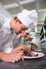 Row of chefs garnishing dessert
