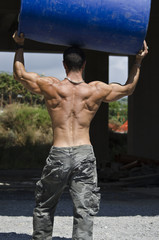 Back of muscular construction worker shirtless in building site