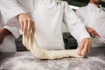 Chefs preparing dough at counter