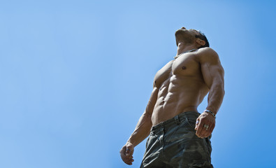 Muscular young male bodybuilder shirtless looking up in the sky