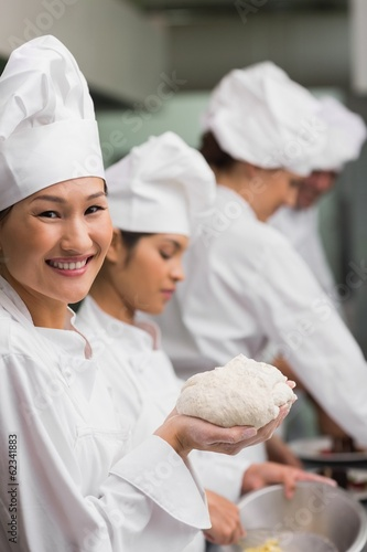 Happy chef holding dough smiling at camera
