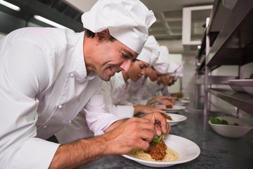 Row of chefs garnishing spaghetti dishes with basil leaf