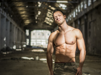 Muscular shirtless young man in abandoned warehouse standing