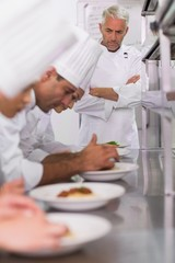 Head chef watching row of chefs garnishing spaghetti dishes with