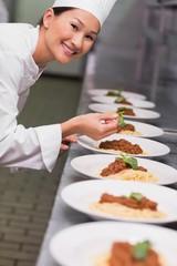 Happy chef putting basil leaf on spaghetti dish