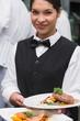 Happy waitress holding steak dinner and salmon dinner