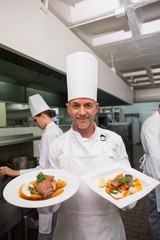Happy chef holding steak dinner and salmon dinner