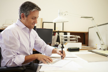 Male Architect Working At Desk In Office