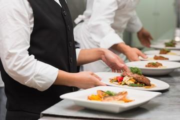 Waitress picking up steak dinner and salmon dinner
