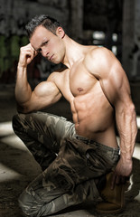 Muscular shirtless young man in abandoned warehouse kneeling