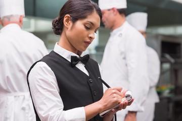 Focused waitress writing on pad