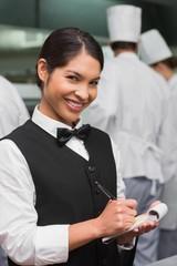 Happy waitress writing on pad