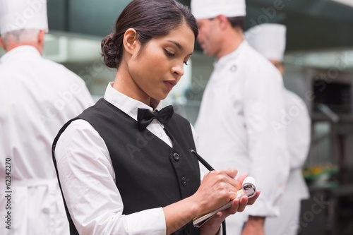 Focused waitress writing on pad