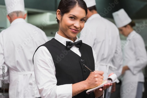 Happy waitress writing on pad