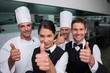 Restaurant team posing together smiling at camera giving thumbs