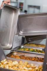 Chefs lifting lids from serving trays