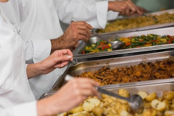 Chefs serving hot food from serving trays