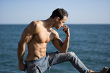Muscular shirtless young man standing by the sea or ocean