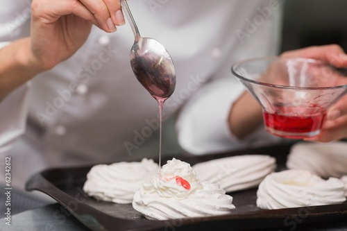 Chef pouring syrup over meringues
