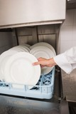 Chef putting plates in drying rack
