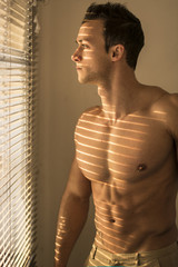 Muscular shirtless man lit by sun behind venetian blinds