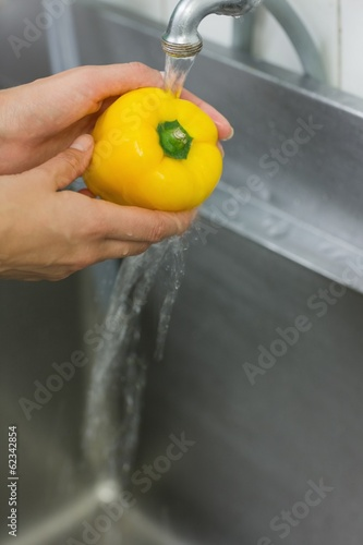Chef washing pepper under the tap