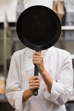 Chef standing covering face with frying pan