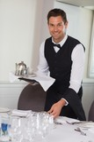 Happy waiter holding tray and setting table