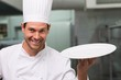 Chef holding a plate smiling at camera