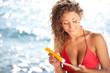 beautiful young woman in bikini smear protective cream on the sk