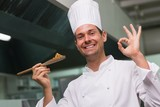 Chef holding a spoon of food and smiling at camera