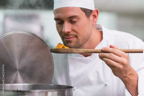 Chef smelling a spoon of food from the pot