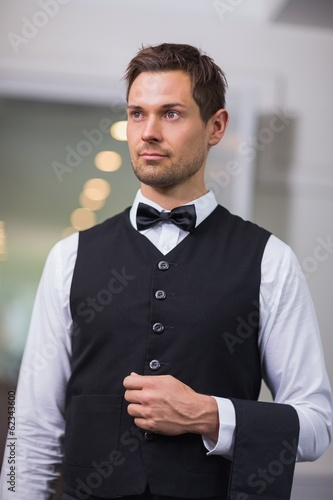 Handsome waiter looking away