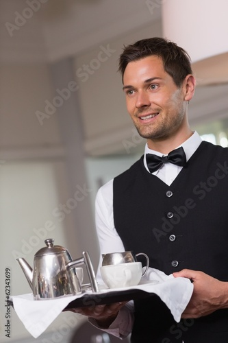 Handsome waiter holding tray with afternoon tea