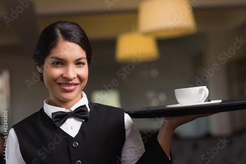 Pretty waitress holding a tray with a cup