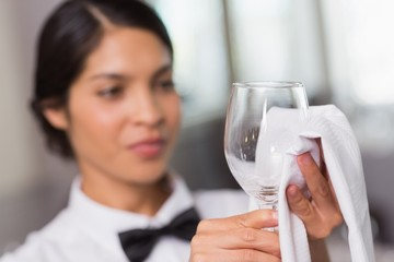 Pretty waitress polishing a wine glass