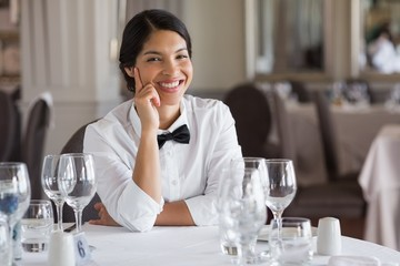 Pretty waitress sitting at set table